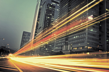 the light trails on the modern building background in city Standard-Bild
