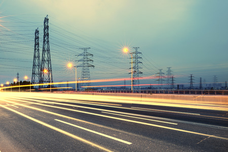 electric grid: high voltage post. High-voltage tower sky background, besides the highway