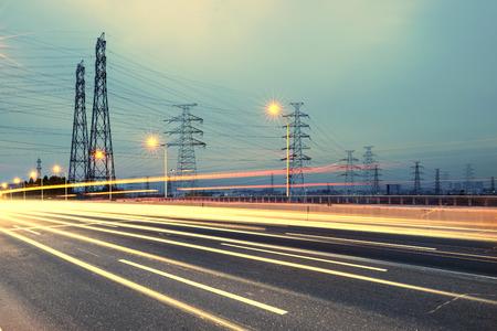electricidad industrial: poste de alta tensión. De alta tensión de la torre del cielo de fondo, además de la carretera Foto de archivo