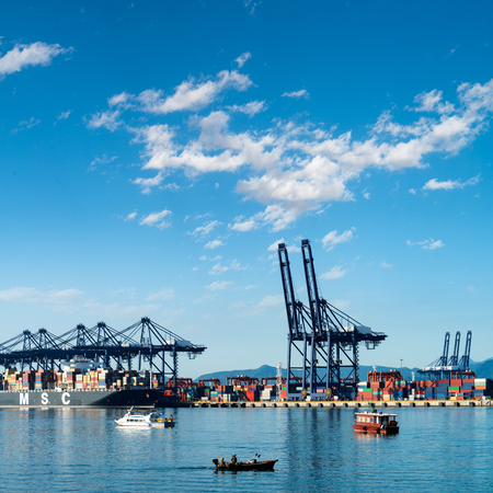 unloading: Container terminal, viewed from the water, on a clear blue day.