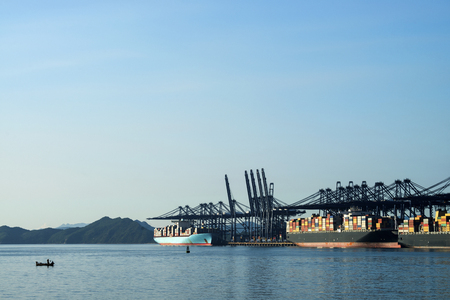 Container terminal, viewed from the water, on a clear blue day.