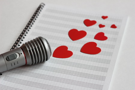 Microphone and paper red hearts are located on a clean music notebook. The concept of music and love. Valentines day