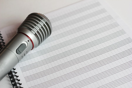The musical microphone lies on a clean sheet music. Music concert. The singer and the song.
