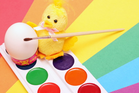 White chicken egg and Yellow chick toy with a brush and water colors on a colored background. The Symbol Of Easter. Imagens