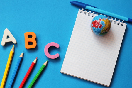 ABC-the first letters of the English alphabet on a blue background. Notebook and pen. Pencils of different colors and small globe. Empty space for text. Learn foreign languages. English for beginners 写真素材