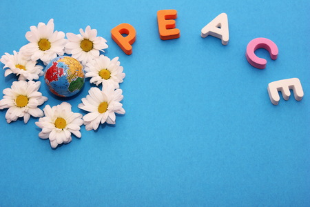Word PEACE made by letters near little figure of a globe surrounded by flowers of white chrysanthemums. Blue background and empty space to insert text. Stock Photo