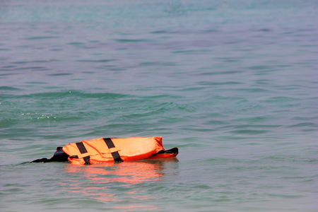 The life jacket floats alone on the surface of the sea. The concept of Safety on the water.