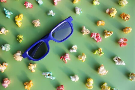 Glasses in blue plastic frame to watch the movie in 3D format among colored popcorn and candy on a green background.