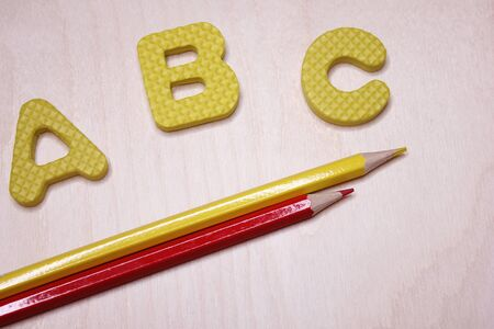 ABC - the first letters of the English alphabet on a light wooden surface next to the yellow and red pencils. Empty space for text. Learn foreign languages. English for beginners. Copy space.