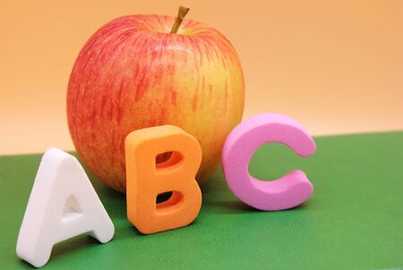 English ABC alphabet letters next to book and apple. Learning foreign language. English for beginners.