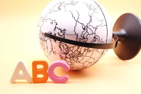 English ABC alphabet letters next to black and white globe. Learning foreign language. English for beginners. International language