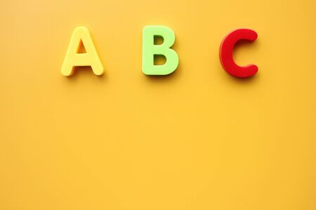ABC first letters of the English alphabet on a yellow background. Empty space for text. Learning foreign language. English for beginners. Copy space.