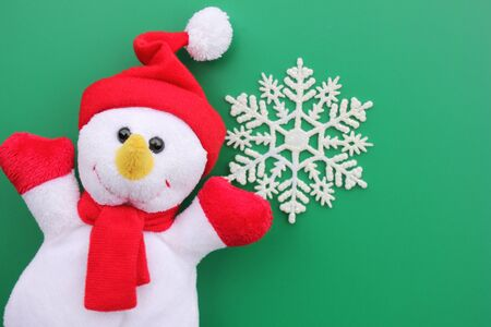 Toy smiling snowman and snowflake on a green background. Christmas background. New year and Christmas concept. Copy Space. Stok Fotoğraf
