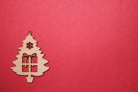 Wooden Christmas tree figurine with a gift on a red background. Copy space. New year and Christmas concept.