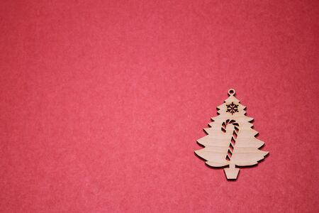 Wooden Christmas tree figurine on a red background. Copy space. New year and Christmas concept. Stok Fotoğraf