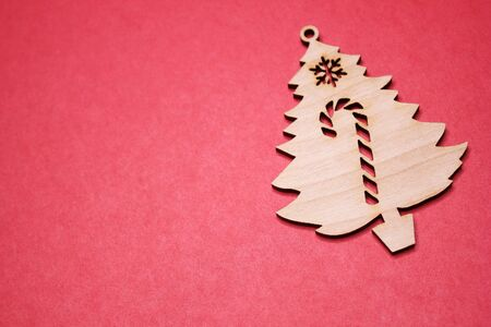 Red Christmas background. Copy space. Wooden Christmas tree figurine on a red background. Copy space. New year and Christmas concept.