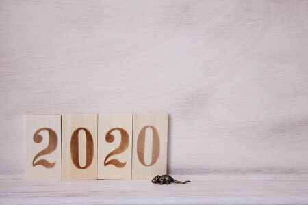 2020 lined with wooden figures on the wooden surface and a little metal mouse next to it. Symbol of the new year 2020 on the Chinese horoscope. Copy space.