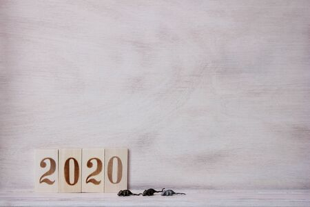 Number 2020 lined with wooden figures on the wooden surface and three little metal mouses next to it. Symbol of the new year 2020 on the Chinese calendar. Copy space. Stok Fotoğraf