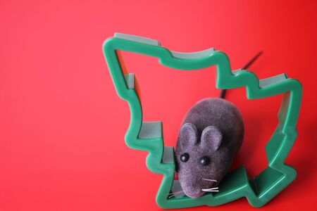 Mouse is a Symbol of new year 2020. Toy mouse and the figure of a Christmas tree on a red background. New year and Christmas concept. Copy space. Stok Fotoğraf