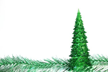 Green toy Christmas tree and tinsel are isolated on white background. Symbol of The new year. Copy space. Stok Fotoğraf