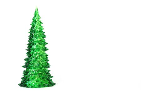 Green toy Christmas tree isolated on white background. Symbol of The new year Copy space.