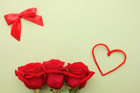 Three red roses with water drops on them . Red bow and heart next to them. Happy Mothers Day. Valentines day holiday. Copy space.