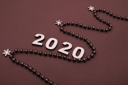 2020 is lined with wooden figures. The figure of the Christmas tree is lined with beads. happy New year