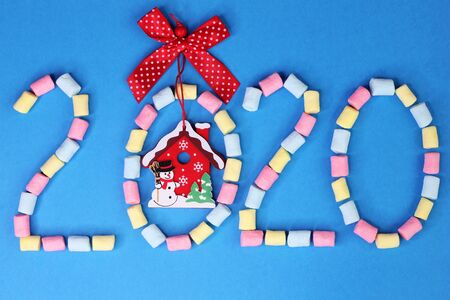 Figures 2020 with red bow and a Christmas toy on them are lined with colored marshmallows on a blue background. Happy New Year.