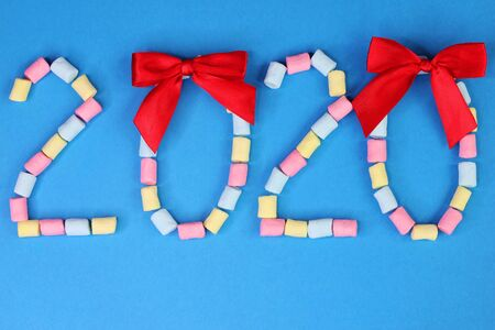 Figures 2020 with red bows on them are lined with colored marshmallows on a blue background. Happy New Year. Stok Fotoğraf