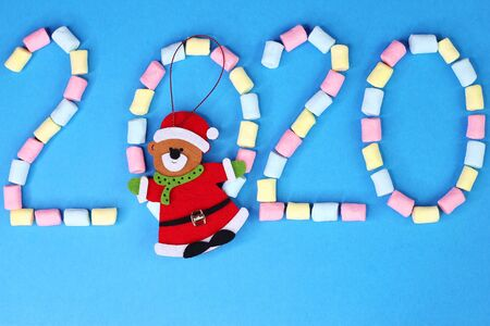 2020 is lined with colored marshmallows on a blue background. Christmas toy bear. Greeting card. New year and Christmas concept.