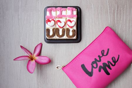 Cakes with the design -I love you-, frangipani flower and cosmetic bag with the inscription-Love me. Valentines day concept.