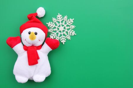 Toy smiling snowman and snowflake on a green background. Christmas background. New year and Christmas concept. Copy Space. Happy New Year.