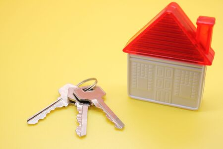 House keys and a plastic toy house on a yellow background. The concept of buying real estate. Stok Fotoğraf - 131434469