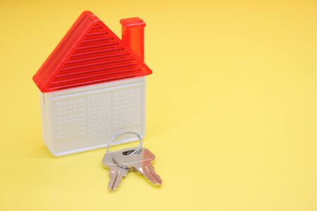 House keys and a plastic toy house on a yellow background. The concept of buying real estate. Copy space. Stok Fotoğraf - 131434476