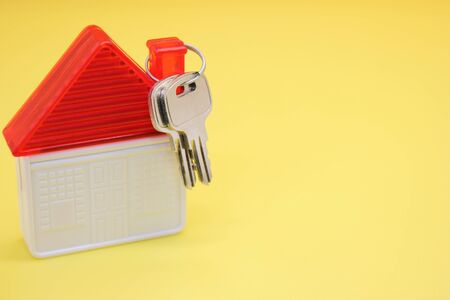 House keys and a plastic toy house on a yellow background. The concept of buying real estate. Copy space.