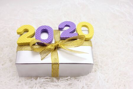 2020 colored numbers on the gift box. The concept of Christmas and the New year.
