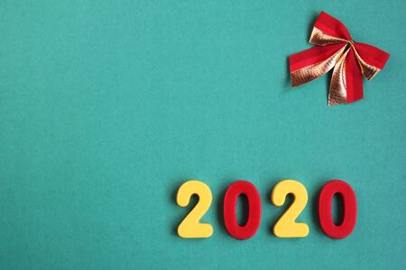 2020 new year numbers and a red bow on a green background. Empty space for text. Happy New Year.