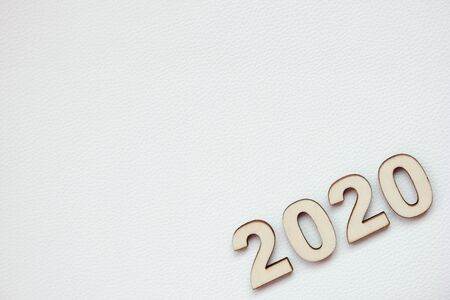 The 2020 new years number is lined with wooden numerals on a white leather surface. Copy space. Stok Fotoğraf