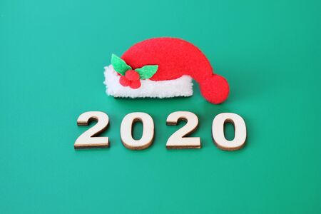 2020 is lined with wooden figures on a green background near a small Christmas hat. Happy New Year. Stok Fotoğraf
