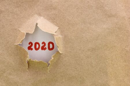 Ripped or torn brown paper revealing new year 2020 on white background. Happy New Year. Copy space. Stok Fotoğraf - 132360753