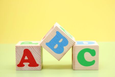 ABC -the first letters of the English alphabet on wooden toy cubes. Learn foreign languages. English for beginners. Copy space. Stok Fotoğraf - 133454002
