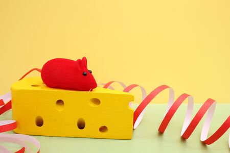 Toy red mouse on toy yellow cheese. Mouse-symbol of New year 2020. Happy New year. Stok Fotoğraf - 132945737