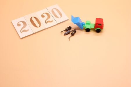 2020 number was lined with wooden figures. A toy dump truck brought and dumped three small metal mice next to it. Symbol of The new year 2020 according to the Chinese calendar. Copy space.