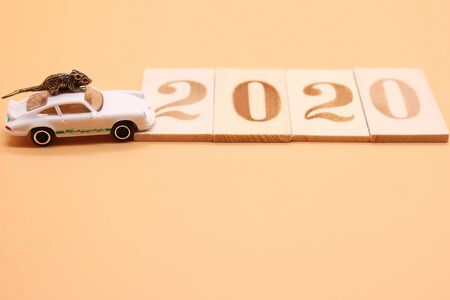 A toy little rat on the roof of a toy car next to the 2020 wooden figurines. Copy space. Stok Fotoğraf - 133454014