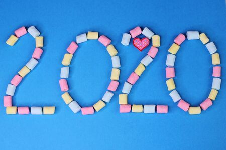 Figures 2020 are lined with colored marshmallows on a blue background. Happy New Year. Stok Fotoğraf - 133454530