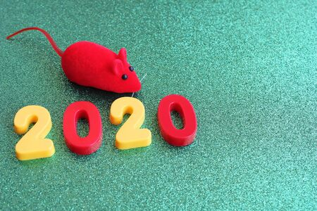 2020 new years number and a toy red mouse on a green background. Mouse-symbol of New year 2020. Happy New year. Stok Fotoğraf - 133454540