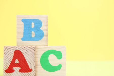 ABC -the first letters of the English alphabet on wooden toy cubes. Learn foreign languages. English for beginners. Copy space. Stok Fotoğraf - 133454539