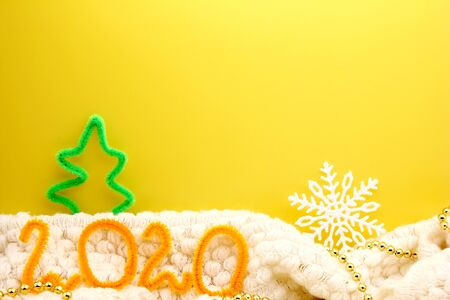 2020 is lined with orange figures on a yellow background near a figure of a small Christmas tree. Happy new year.