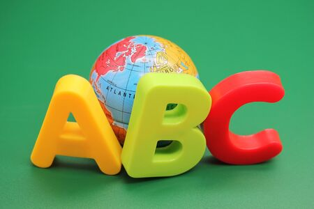 Colored ABC-letters of the English alphabet and small toy globe on a green background. Learning foreign language. English for beginners.