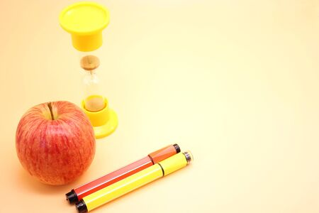 Colored markers red and yellow near the ripe Apple and hourglass. Back to school. Copy space. Stok Fotoğraf